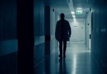 Arzt geht über dunklen Flur eines Krankenhauses. Honorararzt.